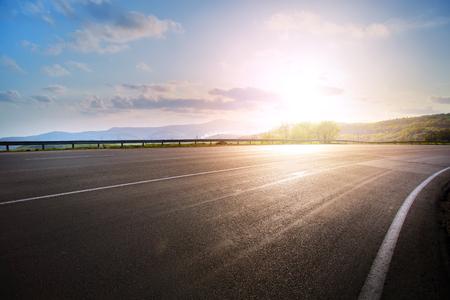 empty asphalt highway road bend and sunset sky