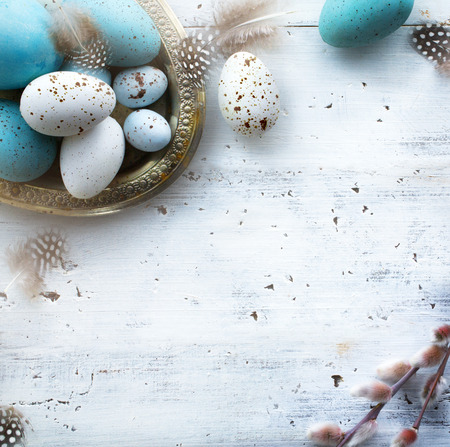 Sunny Easter background with Easter eggs on white table   Imagens