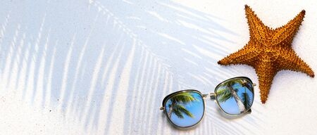 Summer concept, starfish shell and sunglasses on the tropical beach sand, with copy space