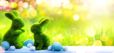Happy Easter Day; Easter rabbit Bunny And Decorated Eggs In Flowery Field