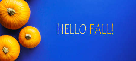 Hello fall message with autumn pumpkin on a blue background