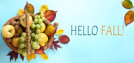 Hello fall message with Autumn leaves, seasonal fruit and Warm scarf on a blue background Stockfoto