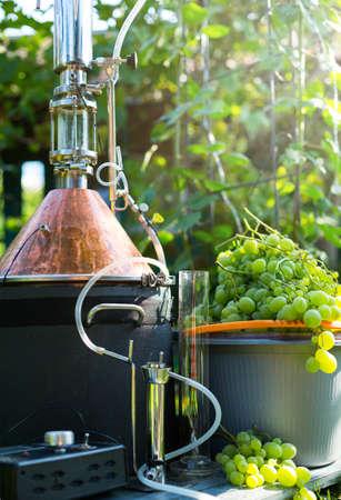 homemade moonshine winemaking; white grape and moonshine still for home brandy production Foto de archivo