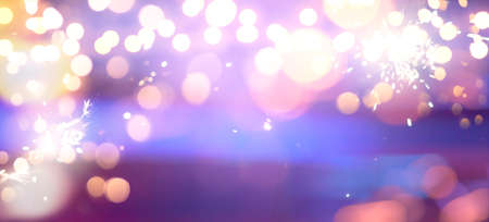 holiday illumination and sparklers - christmas garland bokeh lights over blue background