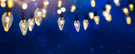holiday illumination and sparklers - christmas garland bokeh lights over snowy blue sky background