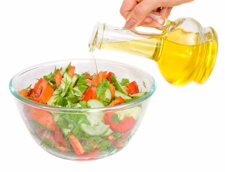 plateful: woman pouring plant oil in vegetarian salad