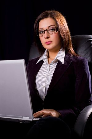 Beautiful young woman in glasses posing with the laptop on dark background Stock Photo - 2791808