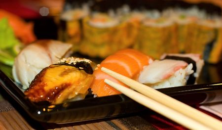 a Japanese dish consisting of small cakes of cold rice with a topping esp of raw fish photo