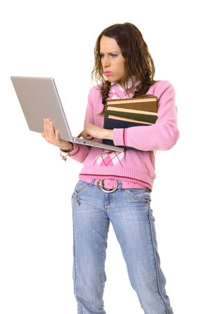 concentrated woman holding laptop and pile of books. isolated on white photo