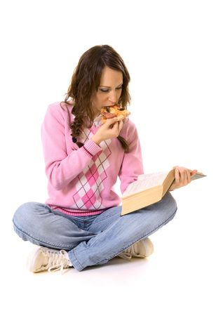 young woman reading the book and eating pizza