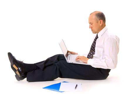 businessman sitting on the floor with laptop and documents photo