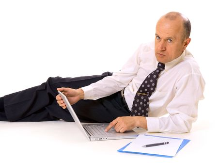 businessman lying on the floor with laptop and documents photo