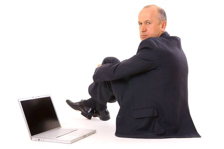 serious businessman sitting on the floor with laptop. isolated on white photo