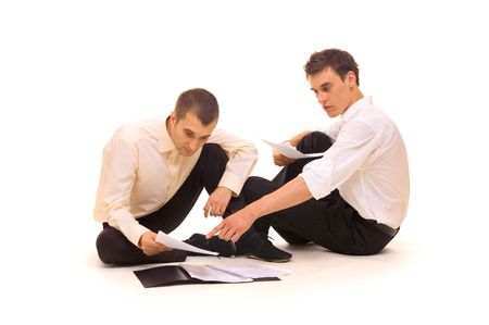 two businessmen sitting on the floor and scrutinizing documents. isolated on white Stock Photo - 3290945