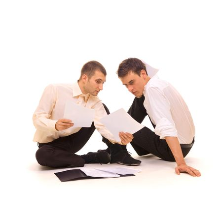 two young businessmen sitting on the floor and making a careful study of documents. isolated on white Stock Photo - 3295256