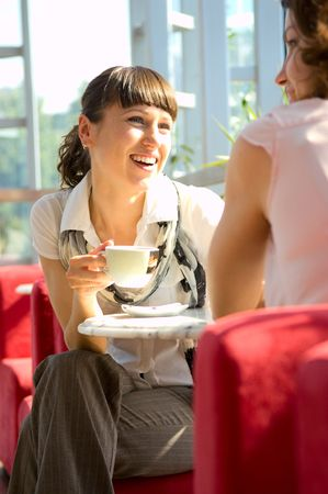 women coffee: two friends have a good time in sunny cafe