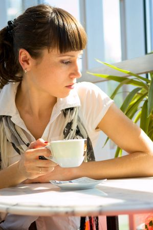 reverie: woman fall into a reverie in sunny cafe