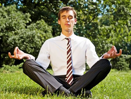 young businessman meditating on the grassland photo