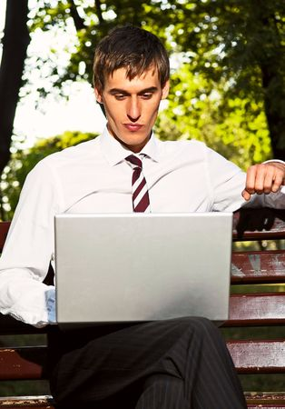 young businessman sitting in the park with laptop photo
