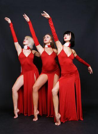 gogo girl: drei T�nzer in roten Abendkleid auf einem dunklen Hintergrund