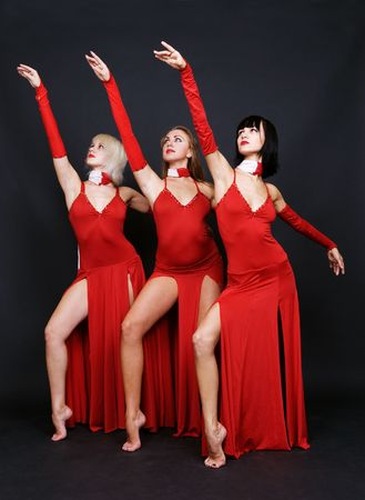 evening gown: three dancers in red evening gown over dark background