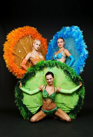 three dancers in stage costumes over dark background photo