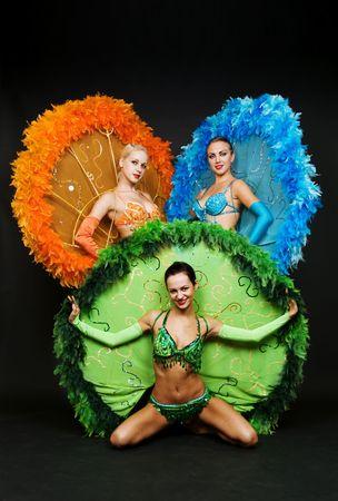 three dancers in stage costumes over dark background