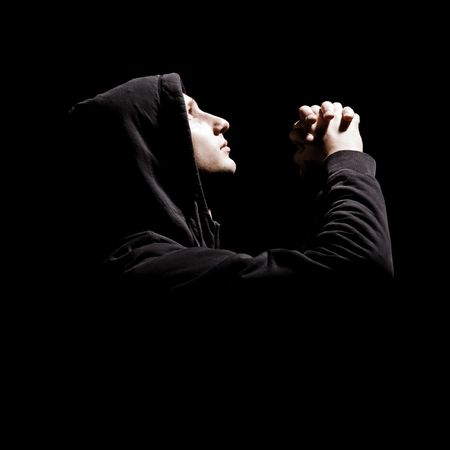 remorse: young man is praying against black background