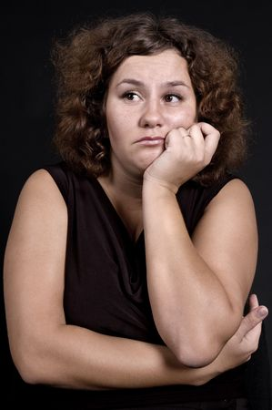 ennui: heavy sad woman against dark background Stock Photo