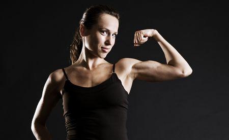 suntanned: muscular woman over dark background