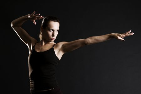 serious sportswoman in pose over dark background