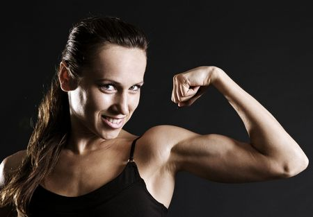 suntanned: smiley sportswoman showing her muscles against dark background Stock Photo