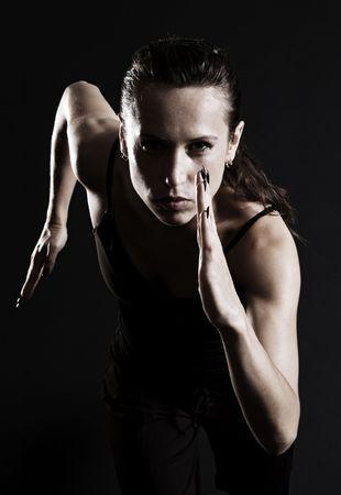 アスリート: 暗い背景の上を走っている女性