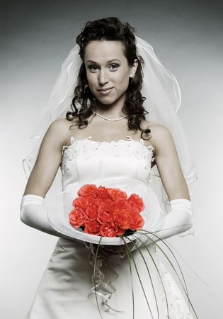 beautiful smiley bride with bunch of flowers over grey background photo