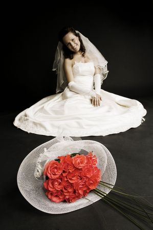 smily bride sitting on the floor with bunch of roses in front of her photo