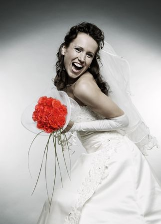 happy bride with bunch of roses over grey background photo