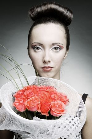 portrait of beautiful woman with bouquet of roses over grey background photo