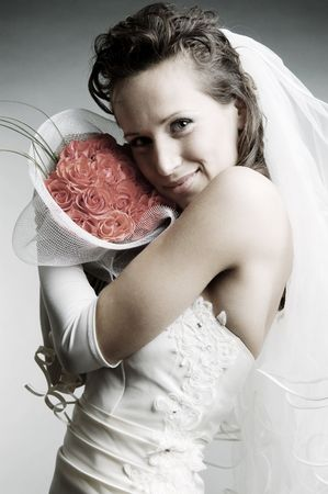 smiley bride holding flowers over grey background photo