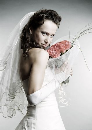 smiley bride with bouquet of flowers over grey background photo