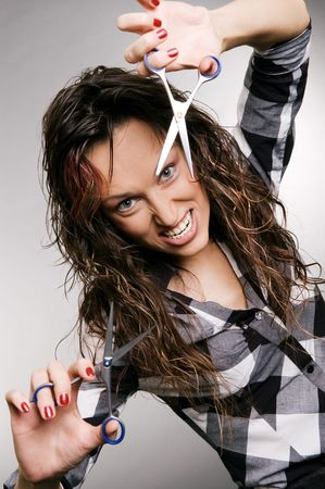 angry hairdresser with scissors over grey background photo