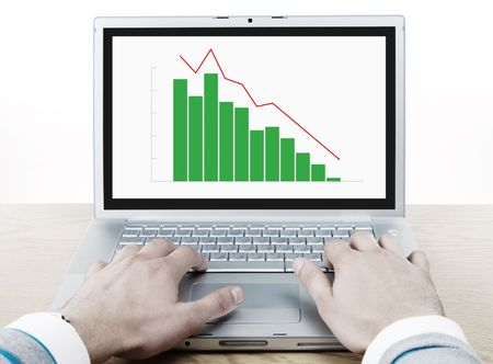 financial crash. man hands on the keyboard of laptop with graph on the display photo