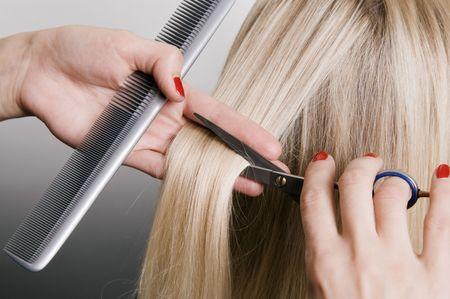 stilist: hairdresser cutting blonde hair. closeup over grey background