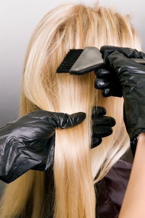 hairdresser doing hair dye. photo against grey background Stock Photo