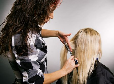 hairdresser working with client. studio shot over grey background Stock Photo - 3704631