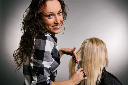 smiley hairdresser with client. studio shot over grey background Stock Photo - 3704613