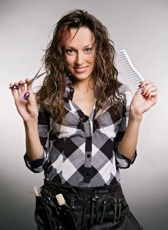 smiley hairdresser with tools against grey background photo