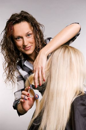 smiley hairdresser working with client. studio shot over grey background Stock Photo - 3704645