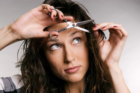 young woman cutting her fringe over grey background photo