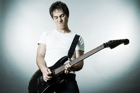 showbusiness: handsome man playing on the guitar. studio shot over grey background