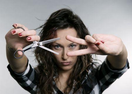 pretty woman with scissors. studio shot photo